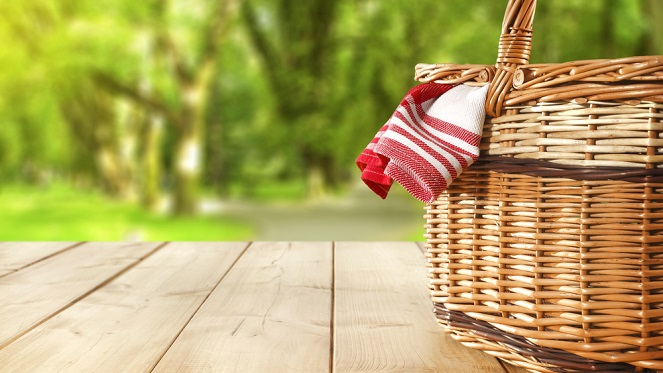 picnic basket sitting on awooden table with a red and white blanket