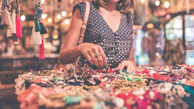 lady shopping at a market looking at colourful jewellery
